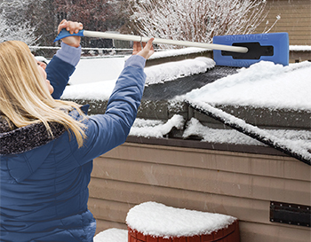 Woman brushing snow off hot tub